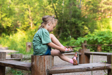 niños vistiendose: Little girl putting her sandal on. She is sitting on a wooden round bench in a summer forest.