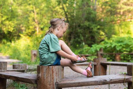 niños vistiendose: Niña de colocar en su sandalia. Ella está sentada en un banco de madera redonda en un bosque de verano. Foto de archivo
