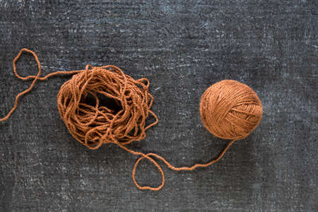 clew: Brown yarn on black grunge background shot from above.