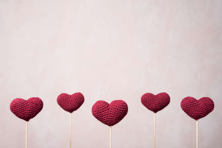 Five crocheted hearts on wooden sticks Stock Photo