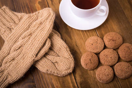 Coffee, mittens and oat cookie on wood Stock Photo