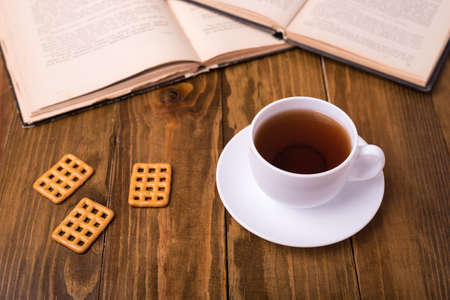 Cup of tea on wooden table with biscuit cookies