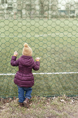 metal grate: Little girl looking at the playing-field through grate