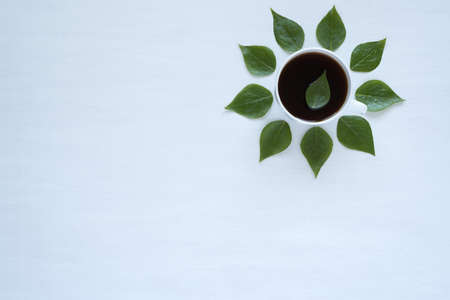 Cup of black coffee and fresh green leaves laying out in circle on white background.