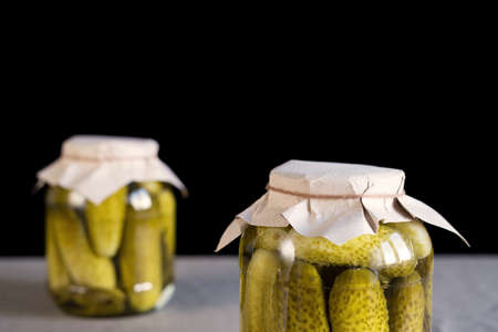 Two closed glass transparent jars with fresh pickled cucumbers placed on a table on black background, homemade preserved vegetables. Banco de Imagens