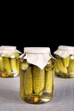Fresh pickled cucumbers on black background