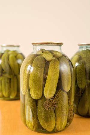Three closed glass transparent jars with fresh pickled cucumbers placed on a wooden table on white background, homemade preserved vegetables.
