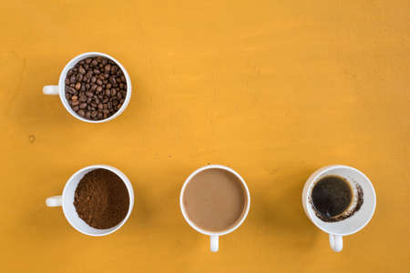 Four different cups on a yellow background. First with coffee beans, second with ground coffee, third with milk coffee and forth with just drunk coffee. Shot overhead. Stock Photo