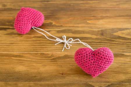 Two crocheted hearts tied together on a wooden table