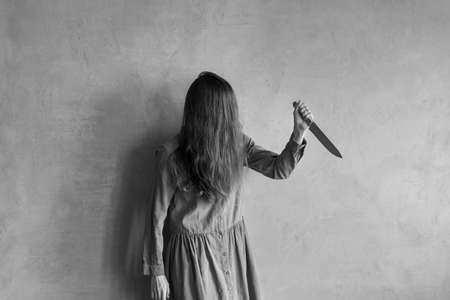 Furious woman with a knife. Her face is covered with hair. Retouched and vignette is added.