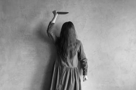 Evil woman with a knife. Her face is covered with hair. Retouched image and vignette is added. Stock Photo