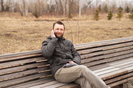 melancholy: Young man talking on a smartphone outdoors