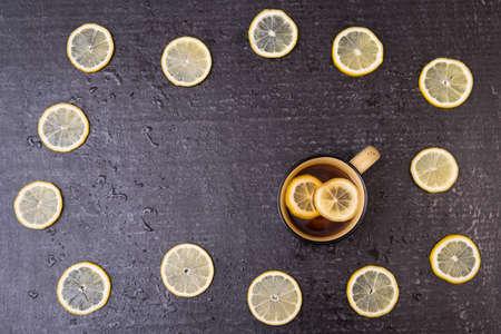 english ethnicity: Big yellow mug with lemon tea and lemon circles on a black shabby background.