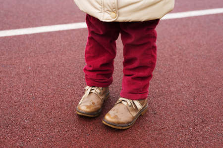 Little girls legs in red jeans and brown boots