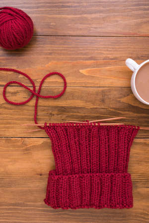 Coffee and red knitting on wooden background Stock Photo