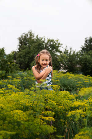 Little girl hugging herself in a summer garden Stok Fotoğraf