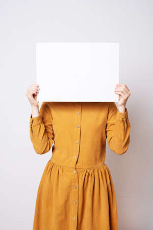 Beautiful woman in a yellow old-fashioned dress holding a blank sheet of paper. Stok Fotoğraf