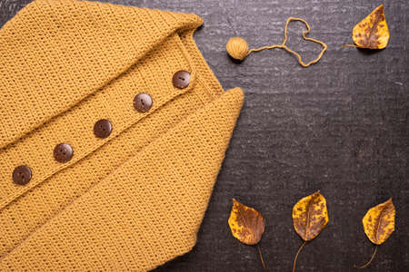 Autumn composition with a yellow crocheted cardigan, dried leaves and a small ball of yarn on a black background.