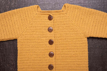 Autumn composition with a yellow crocheted cardigan on a black background.