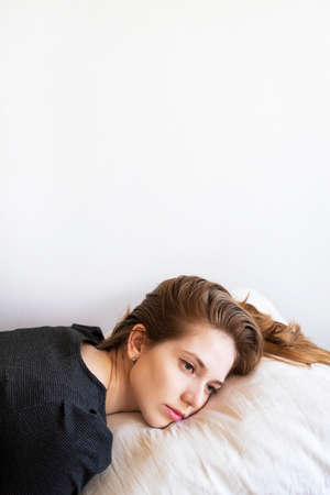 Vertical portrait of young beautiful sad woman on a pillow