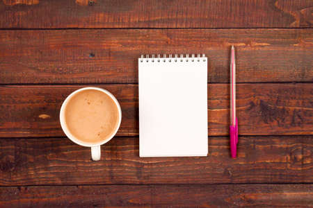 Flatlay background with a cup of coffee, a pink pen and a notebook on a wooden board. Standard-Bild