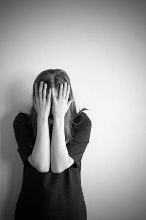 Vertical monochrome portrait of young beautiful woman in depression