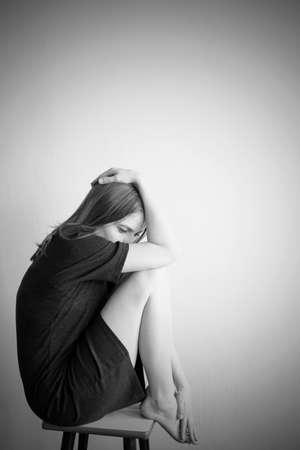 Vertical monochrome portrait of young beautiful woman in depression Standard-Bild