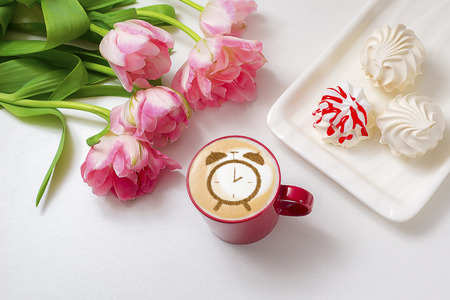 cup of cappuccino with pattern of cinnamon clock on milk foam