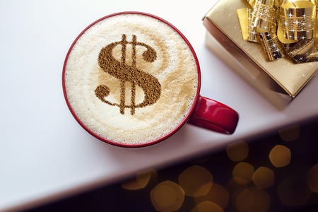 cup of coffee cappuccino with a picture of a dollar sign from cinnamon on milk foam