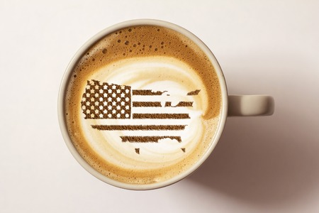 Flag of the United States of America in the form of territorial borders on a cappuccino coffee cup close-up Stok Fotoğraf