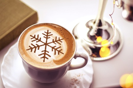Cappuccino with a pattern of snowflakes from cinnamon on milk foam during Christmas holidays coffee for christmas