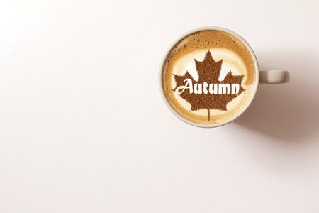 a cup of coffee cappuccino with the inscription autumn from cinnamon on milk foam