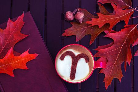 zodiac sign Aries on a foam of hot cappuccino in a white cup and stars on a dark table