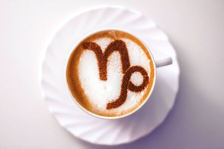 A cup of cappuccino coffee with a zodiac sign of Capricorn Cinnamon on milk foam