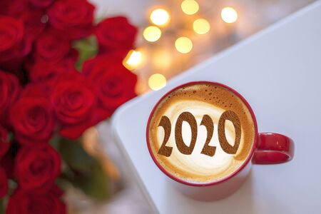 Figures 2020 as a symbol of the New Year on cups of hot aromatic coffee on a bright red background among stars and marshmallows. Top view, flat lay