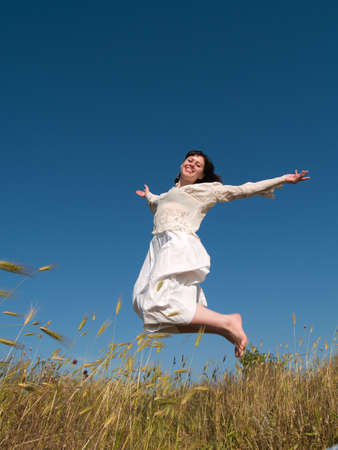 Happy jumping girl in green field on blue sky  photo