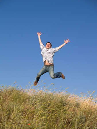 Happy jumping male teenager above green grass hill Stock Photo