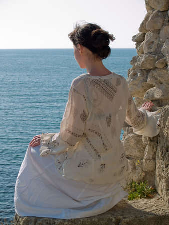 lonely young woman looking on sea white dress sitting on stone
