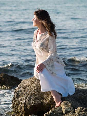 Beautiful young lady sitting on sea stone ethnic dress photo