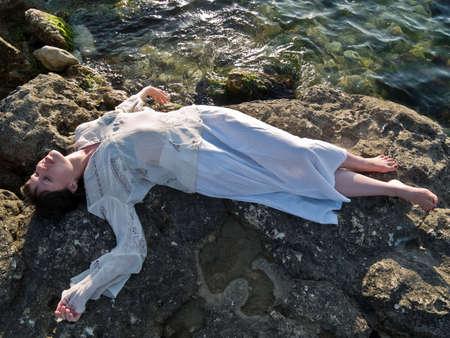 ethnic dress: Bellissima giovane donna giace sul mare rock etnico abito