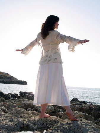 Beautiful young lady dancing on rocky sea shore photo