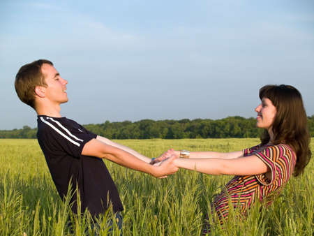 Teen Couple Holding hands Field looking each other