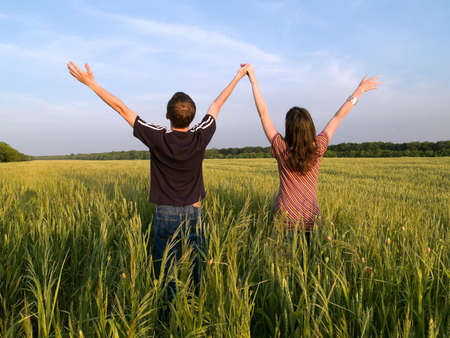 woman looking up: Young Couple in Field Holding Hands Up Rear View Stock Photo