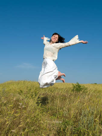 Happy Jumping Girl on Field looking to camera Stock Photo