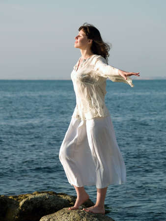 Young beautiful barefoot woman staying on sea stone arms outstretched