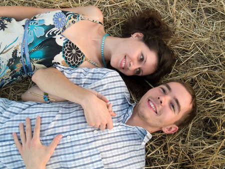 Lovely young couple lying in stray in filed photo