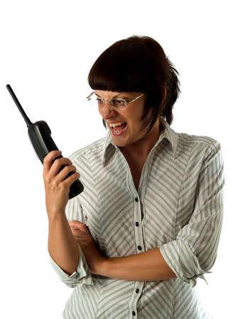 Irritated young female secretary screaming to cordless phone photo