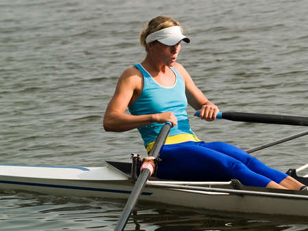 rowing boat: Sporty young lady rowing in boat on water