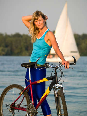 Young female blond cyclist staying looking to camera smiling
