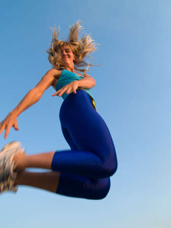 Beautiful fit blond girl jumping smiling cheerful Stock Photo - 3498971